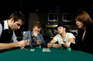 Four friends playing poker together in bar